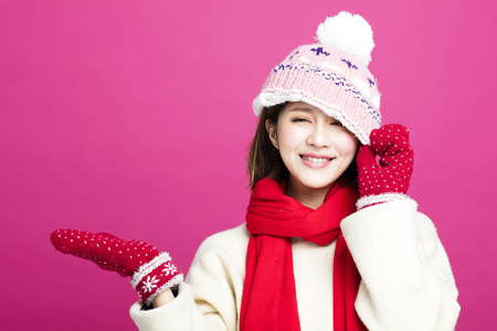 Young Beautiful Woman in winter clothes and showing something